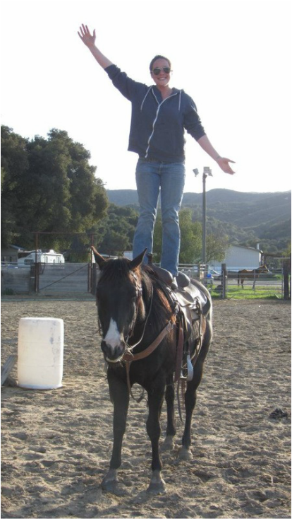 Anna Thomas standing on a horse